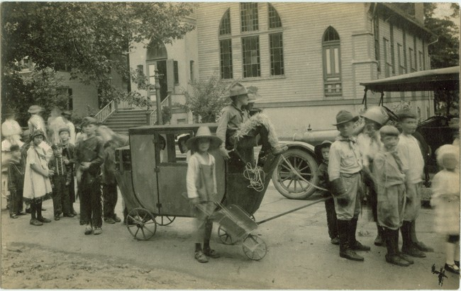 A parade of young people and cars, circa 1925